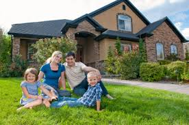 Family sitting in grass in front of newly constructed home.